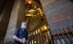 A tourist wearing protective mask walks in front of giant Buddha at Wat Pho temple in Bangkok, Thailand