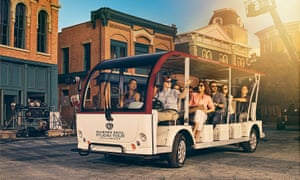 A publicity image of guests in a tour cart on the lot at the Warner Bros studio tour in Hollywood, Los Angeles, US.