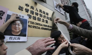 Protesters stick photos of the missing booksellers outside a government office in Hong Kong