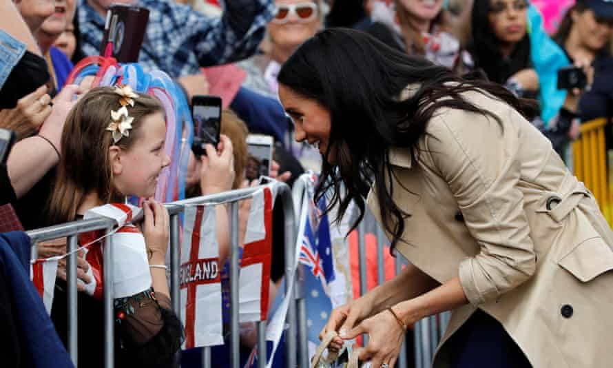 Meghan, Duchess of Sussex speaks to a girl in the crowd.