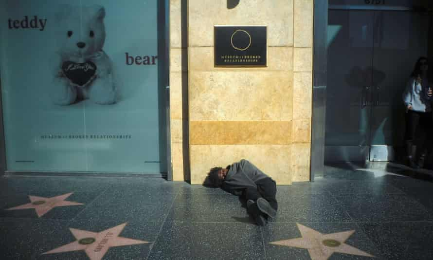 A man sleeps on the sidewalk in Hollywood. Tens of thousands of people are homeless in California.