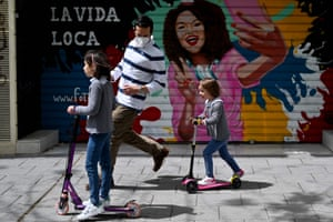 Children ride scooters accompanied by an adult in Madrid