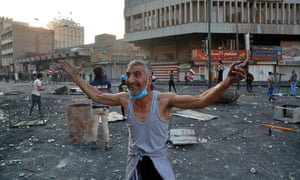 A man gestures at fellow demonstrators to join the protest during clashes with Iraqi security forces at Khilani Square in Baghdad.
