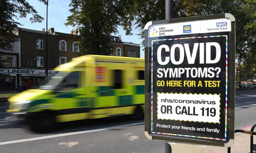An ambulance drives past a sign displaying a Covid helpline in London.