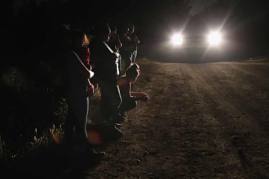 Central American asylum seekers wait for transport while being detained near the US-Mexico border