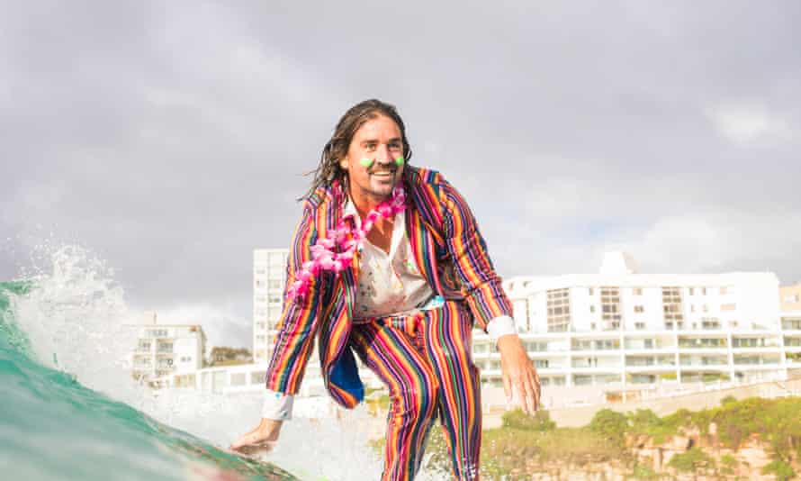 Grant Trebilco in a rainbow suit, surfing