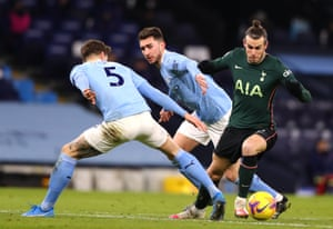 Gareth Bale of Tottenham Hotspur gets through the challenges of Aymeric Laporte and John Stones of Manchester City.
