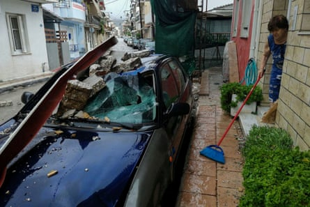 A woman removes water from the entrance of her house as a car is seen under the debris
