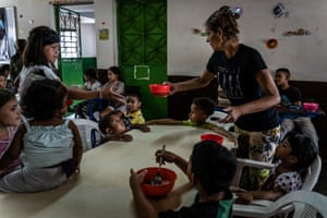 Community volunteers help serve food to children at a kitchen run by Alimenta la Solidaridad, a local NGO working in Petare, in February 2019