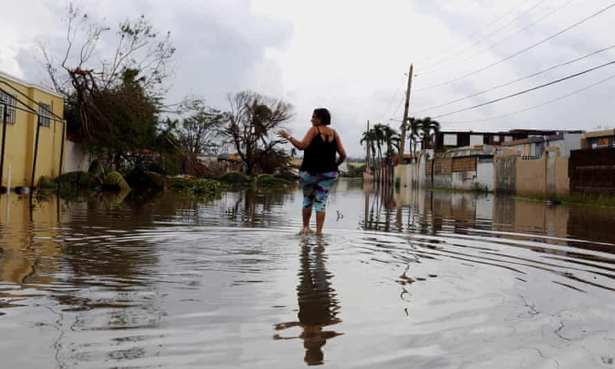 A woman walks on a flooded Puerto Rico street in the aftermath of Hurricane Maria.
