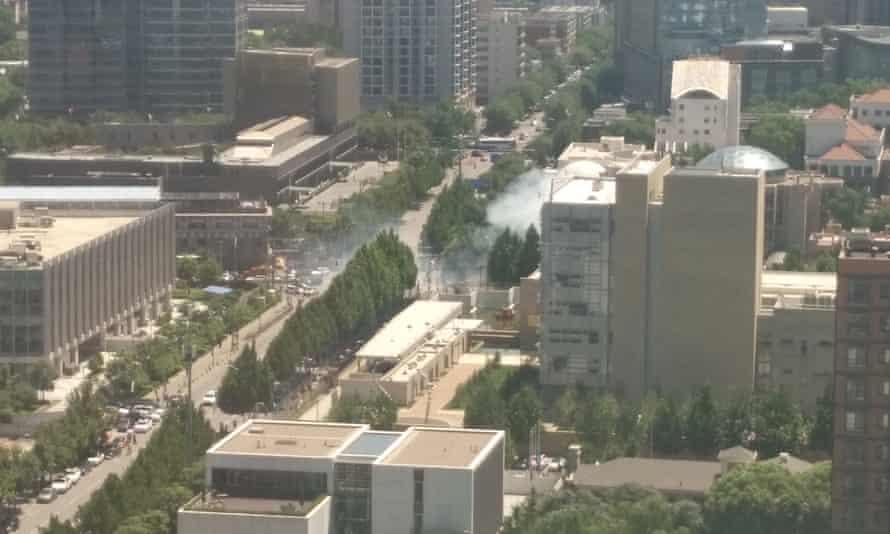 Smoke rises from a street corner near the US embassy in Beijing