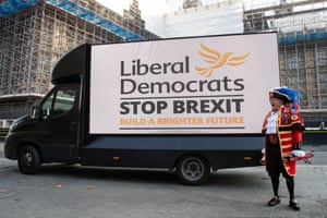 London, England The town crier Tony Appleton stands in front of a digital screen as it displays the new Liberal Democrat election campaign slogan on the back of a van outside the Houses of Parliament