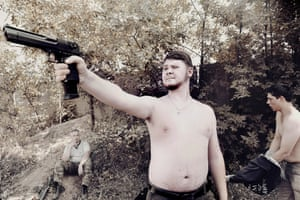 A young man plays with his pistol during a life-size military game imitating the war in Syria and organised by the Ministry of Defence of the Donetsk People's Republic. On either side of the front line, youth recruitment becomes a real propaganda tool