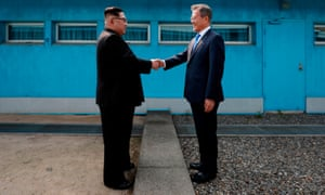 North Korea's leader Kim Jong Un (L) shakes hands with South Korea's President Moon Jae-in (R) at the Military Demarcation Line that divides their countries ahead of a summit in April 2018.