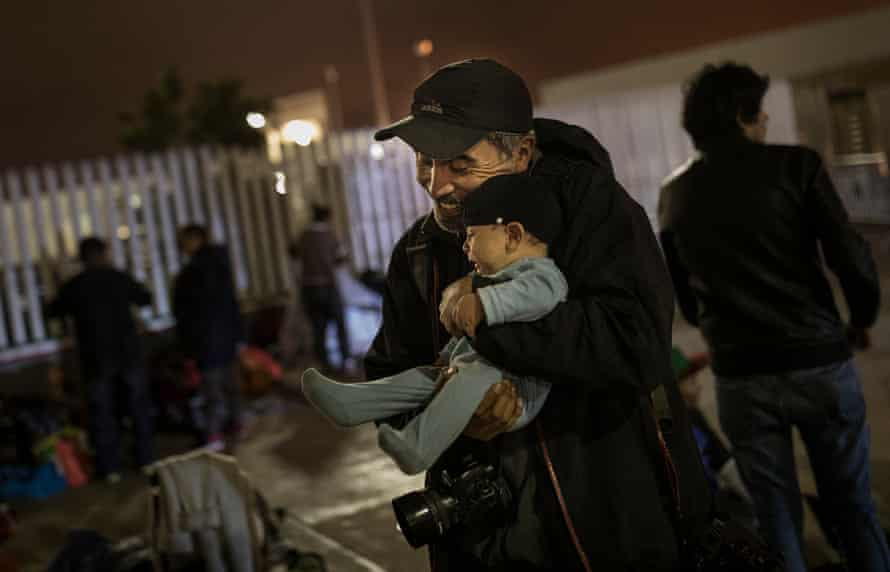 Edgard Garrido holding baby - for use in photo essay about the migrant caravan