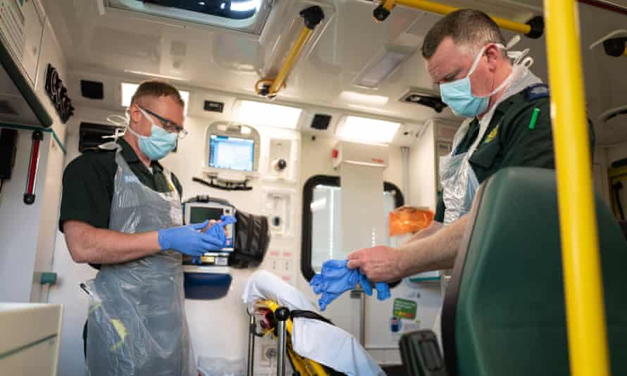 Paramedics responding to a 999 call don their protective clothing.