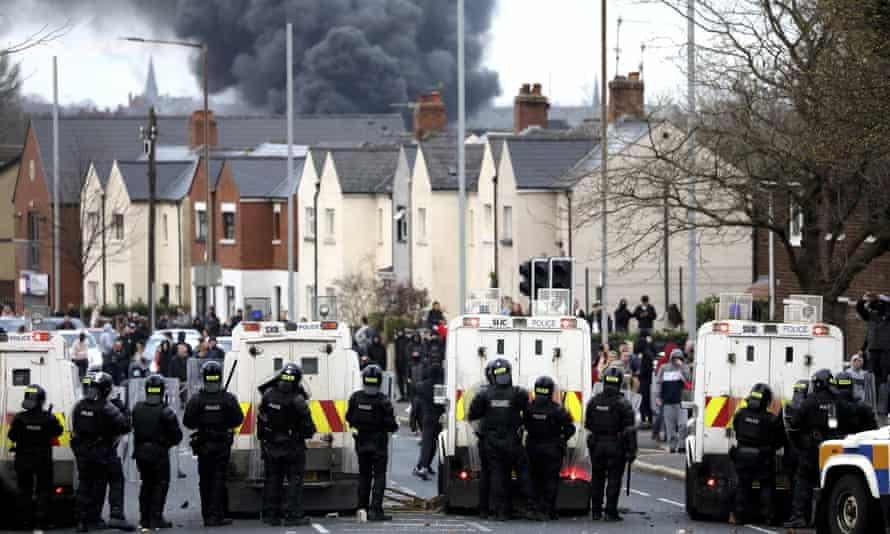 Police form a line on the Springfield in Belfast, Northern Ireland.