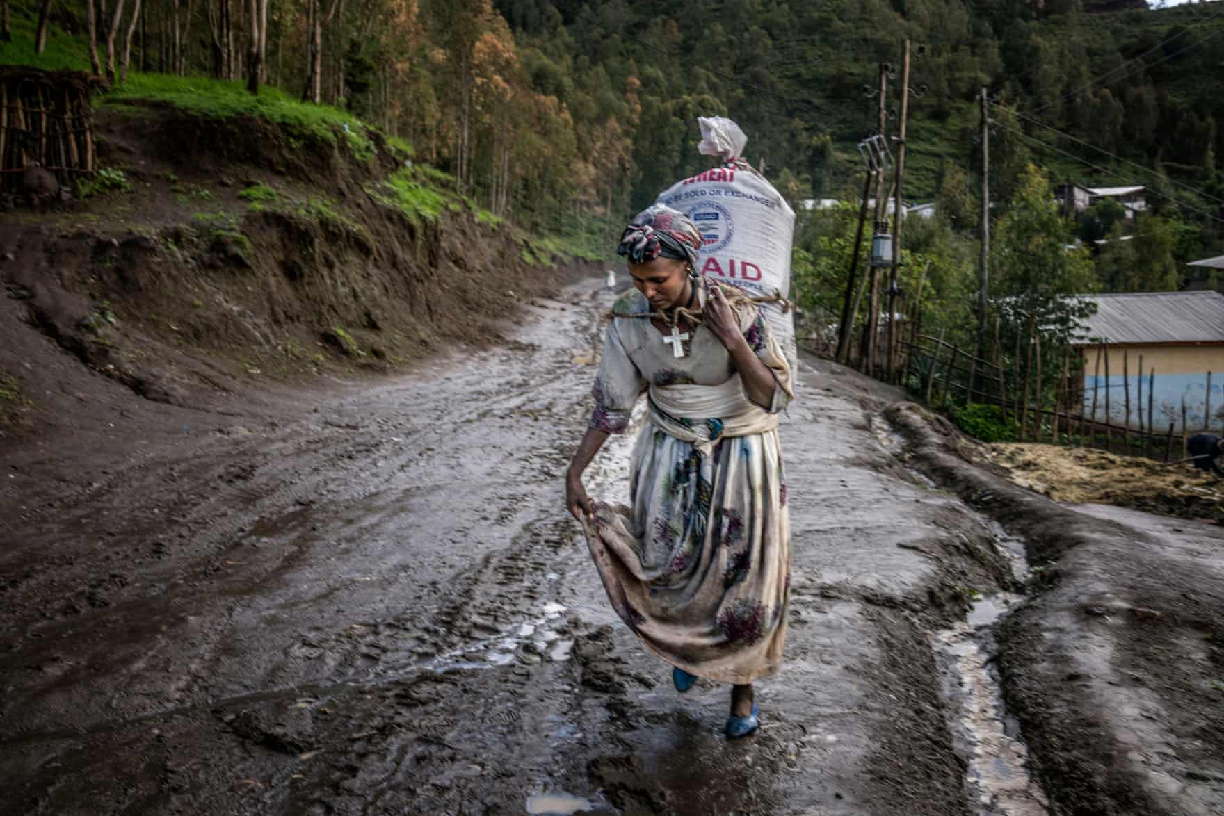 A woman carries a heavy sack of wheat along a saturated road. Unusually heavy summer rains have caused severe flooding, displacing almost 190,000 people via The Guardian