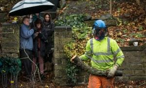 Residents watch contractors cut down a tree in Rustlings Road, Sheffield.