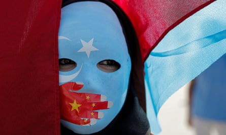An ethnic Uighur demonstrator wears a mask as she attends a protest against China in front of the Chinese Consulate in Istanbul, Turkey.