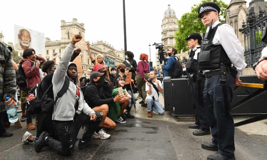 Protesters kneel in front of police during the Black Lives Matter protest.