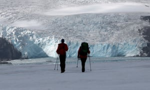 Two scientists walk towards the Collins Glacier on King George Island in the South Shetland Islands, Antarctica
