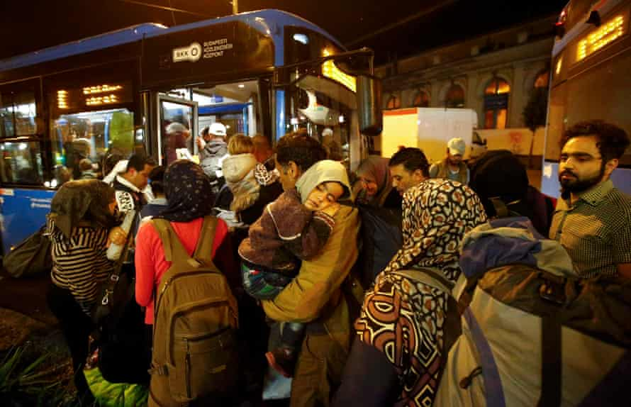 Migrants enter a bus, which is due to leave Keleti train station in Budapest on route for Austria