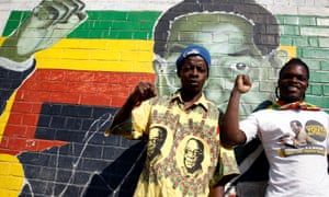 Youths stand besides a mural in Harare depicting Robert Mugabe after hearing the news of his death