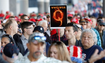 A man in the crowd holds a QAnon sign as crowds gather to attend Donald Trump's campaign rally in Las Vegas, Nevada, 21 February 2020.