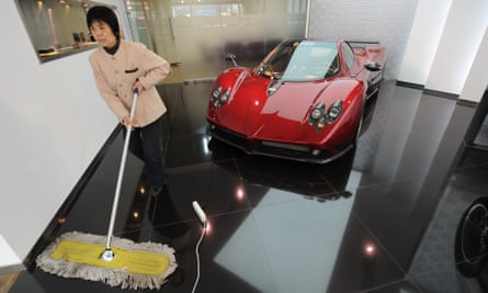 A cleaner sweeps the floor next to a Pagani sportscar in a luxury car showroom in Beijing.