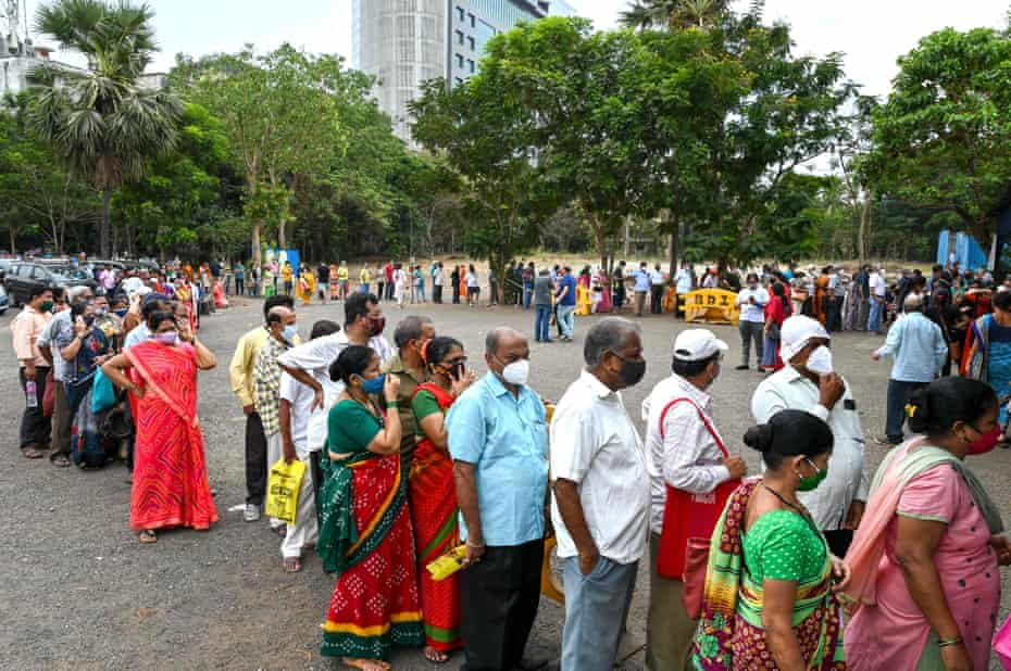 People wait in queues to receive the vaccine at a vaccination centre in Mumbai 21 April