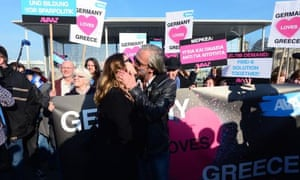 A German woman and a Greek man stage a 'kiss marathon' in front of the chancellery in Berlin prior to a meeting of the leaders of Greece and Germany on March 23, 2015. AFP PHOTO / JOHN MACDOUGALLJOHN MACDOUGALL/AFP/Getty Images