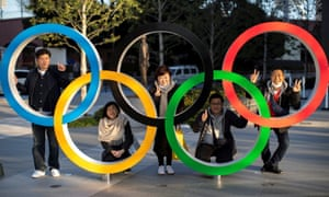 Fans pose for photographs with the Olympic rings in front of the Japan Olympic Museum in Tokyo on Monday.