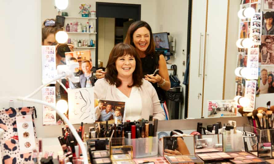 Coleen Nolan sitting, with her makeup artist standing behind her, seen in the mirror of her dressing room, lots of makeup on the table in front of them