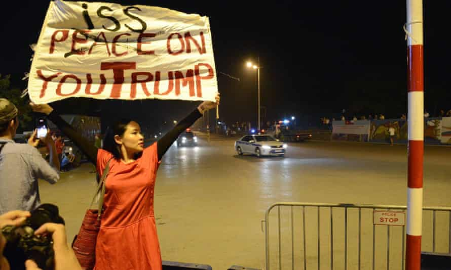Vietnam dissident musician Mai Khoi holds up a banner reading 'Piss on you Trump' in Hanoi as the US president's motorcade passes.