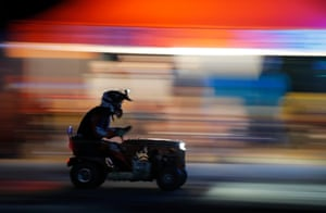 A driver speeds past the pits in the middle of the night. Like al of the other racers, this mower has no suspension.
