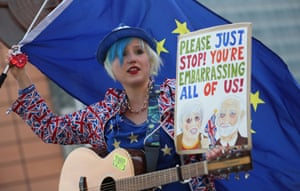 A street musician waves an EU flag and carries a placard saying 'Please just stop! You're embarrassing all of us!' as she performs ahead of a European Council meeting on Brexit, April 2019