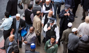 Policemen pass through Muslims leaving the East London Mosque after Friday prayers.