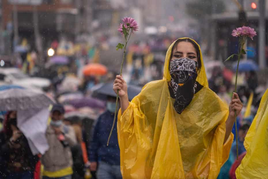 A protester holds a flower while marching in the rain in Bogotá, Colombia, on May 5.
