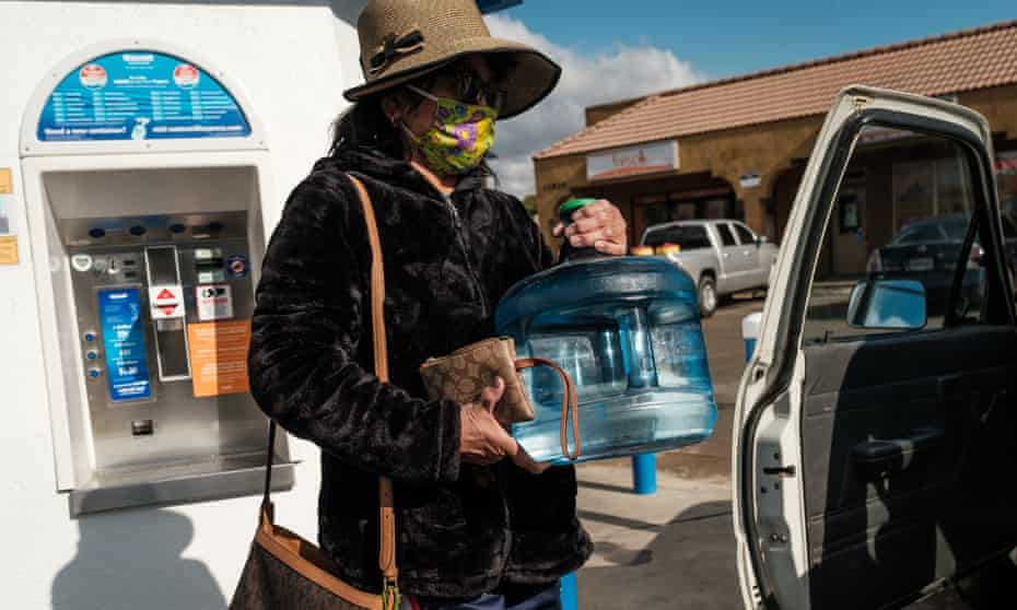 A woman fills up drinking water containers from a kiosk in Orosi.