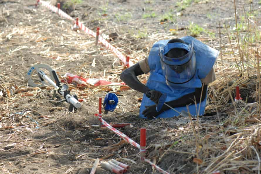A deminer manually removes a mine.