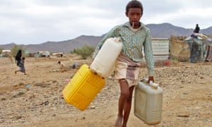 A displaced child carries water at a camp in Yemen