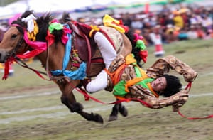 A rider performs horsemanship during a horse racing festival in the province of Litang, China.