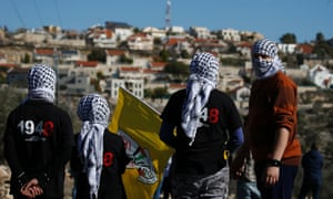 Palestinian protesters face an Israeli settlement in the West Bank in December.