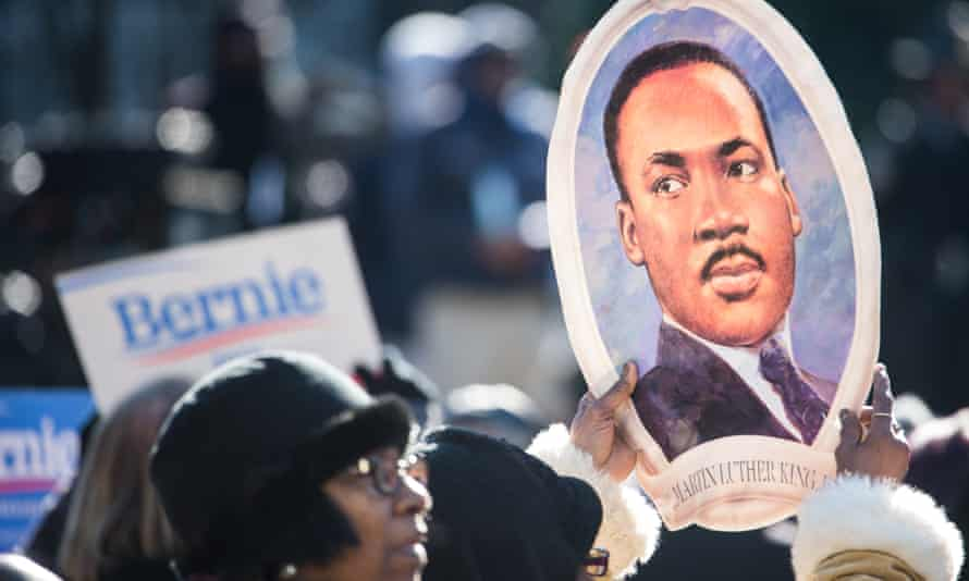 A woman holds a portrait of Martin Luther King during the King Day at the Dome rally on Monday.