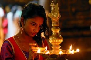 A devotee lights oil lamps at a religious ceremony in Colombo, Sri Lanka