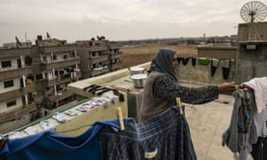 A woman hangs out laundry in the Syrian border town of Ras al-Ayn