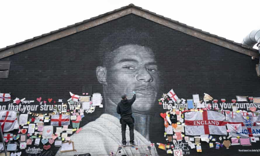 Street artist Akse repairs the mural of Marcus Rashford on the wall of the Coffee House cafe on Copson Street, in Withington, Manchester.