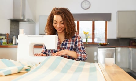 Woman at kitchen table using sewing machine. A woman makes curtains at home using a sewing machine.