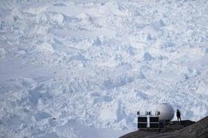 A woman stands next to an antenna at an NYU base camp at the Helheim glacier.